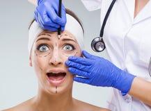 Bello fronte della donna, con le marcature chirurgiche quando sguardo fatto sussultare Fotografie Stock Libere da Diritti