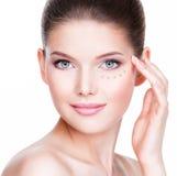 Bello fronte della giovane donna con il fondamento cosmetico su una pelle Fotografie Stock Libere da Diritti