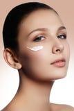 Bello fronte di giovane donna con crema cosmetica su una guancica La SK immagini stock
