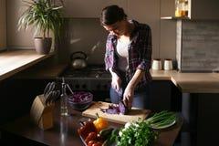 Bello funzionamento castana nella cucina La donna taglia le verdure Vegetariano e stile di vita sano fotografia stock