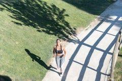Bello funzionamento della giovane donna che pareggia in un listeni del parco all'aperto Fotografia Stock