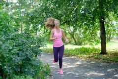 Bello funzionamento della giovane donna nel parco verde il giorno di estate soleggiato immagine stock libera da diritti