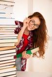 Bello geek attraente della donna nello studio con il mucchio dei libri Immagini Stock