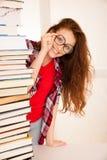 Bello geek attraente della donna nello studio con il mucchio dei libri Fotografie Stock Libere da Diritti