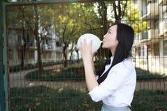 Bello gioco adorabile sveglio dello studente di college della High School della ragazza sul pallone del colpo del campo da giuoco Immagini Stock Libere da Diritti