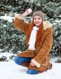 Bello gioco della donna con neve sull'inverno all'aperto, abeti nevosi in foresta, capelli rossi lunghi, portanti un cappotto di  Fotografia Stock