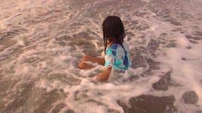 Bello gioco indonesiano asiatico felice della ragazza del bambino del movimento lento spensierato sulla spiaggia divertendosi nel stock footage