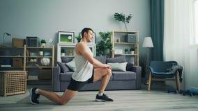 Bello giovane in abiti sportivi che fanno gli esercizi a casa che allungano le gambe archivi video