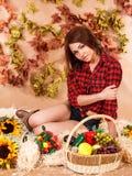 Bello giovane agricoltore femminile che si siede in un fieno con un raccolto Immagini Stock