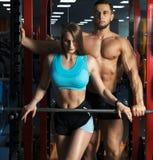 Bello giovane allenamento sexy sportivo delle coppie in palestra Fotografie Stock Libere da Diritti