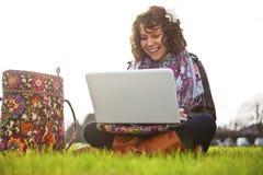 Bello giovane allievo che per mezzo del computer portatile su erba Immagini Stock Libere da Diritti