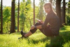 Bello giovane atleta femminile che usando forma fisica app sul suo orologio astuto per controllare prestazione di allenamento Tec Fotografia Stock