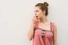 Bello giovane brunette che mangia lo spuntino del cioccolato. Fotografia Stock