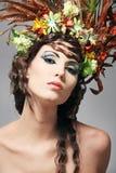 Bello giovane brunette con i fiori in capelli. fotografia stock
