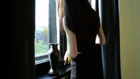 Bello giovane castana in vestito nero va allo studio e mette i fiori in un vaso archivi video