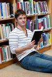 Bello giovane che tiene un libro sul pavimento Immagini Stock