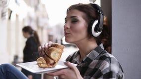 Bello, giovane donna che si siede accanto alla finestra in grandi cuffie Ascolti la musica ed il cibo del croissant tenuta stock footage