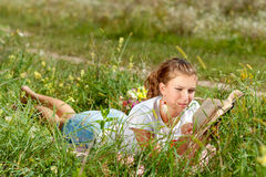 Bello giovane donna-studente che legge un libro che si trova sull'erba Ragazza graziosa all'aperto nell'estate Fotografia Stock Libera da Diritti