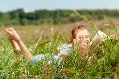 Bello giovane donna-studente che legge un libro che si trova sull'erba Ragazza graziosa all'aperto nell'estate Fotografia Stock