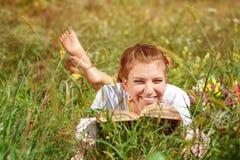 Bello giovane donna-studente che legge un libro che si trova sull'erba Ragazza graziosa all'aperto nell'estate Immagini Stock