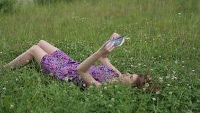 Bello giovane libro di lettura dello donna-studente su erba stock footage