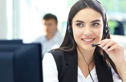 Bello giovane operatore di call center femminile con la cuffia avricolare in ufficio Fotografia Stock Libera da Diritti