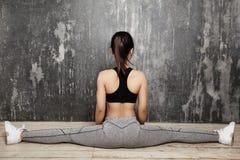 Bello giovane risolvere asiatico della donna, facente esercizio di Pilates in abiti sportivi Spaccature con yoga Asana, allungant Fotografia Stock Libera da Diritti