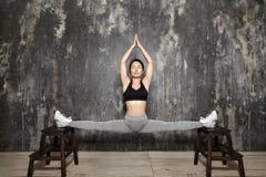 Bello giovane risolvere asiatico della donna, facente esercizio di Pilates in abiti sportivi Spaccature con yoga Asana, allungant Fotografie Stock Libere da Diritti