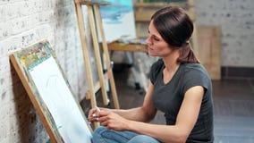 Bello giovane schizzo messo a fuoco del disegno della donna del progettista su tela facendo uso del colpo di medium grigio della  video d archivio