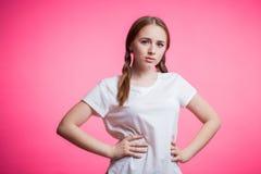 Bello giovane scolaro, ragazza dello studente con i vetri rotondi e treccia che esamina la macchina fotografica su un rosa fotografie stock