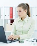Bello giovane segretario che lavora al computer portatile che si siede all'ufficio Immagine Stock