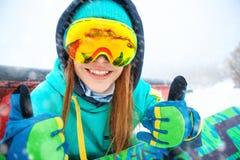Bello giovane snowboarder felice che si siede con il suo snowboard immagine stock