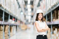 Bello giovane sorridere asiatico del tecnico o dell'ingegnere, fondo della sfuocatura della fabbrica o del magazzino, industria o fotografia stock