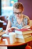 Bello giovane studente con i lotti dei libri Immagini Stock