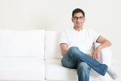 Bello giovane tipo indiano che si siede sul sofà Immagine Stock Libera da Diritti