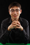 Bello giovane uomo sorridente in camicia nera e vetri che si siedono a Immagini Stock