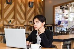 Bello giovane uso della donna di affari un computer portatile lavorare in una caffetteria Fotografia Stock