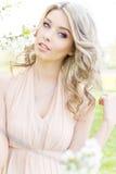 Bello giovane volo dolce tenero della ragazza in un vestito leggero che cammina in un frutteto di ciliegia fertile Fotografia Stock