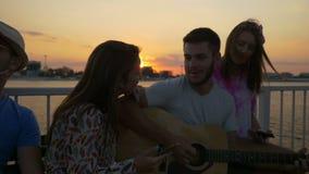 Bello gruppo di adolescenti che cantano felicemente alla spiaggia video d archivio