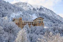 Bello hotel di Solis Soci circondato con gli alberi forestali nevosi su un paesaggio scenico di montagna del fondo soleggiato del Immagine Stock Libera da Diritti