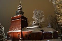 Bello illuminato nella chiesa di legno di notte nell'inverno in pieno di neve Tylicz Polonia immagini stock
