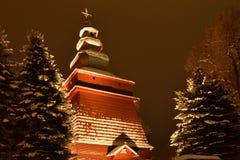 Bello illuminato nella chiesa di legno di notte nell'inverno in pieno di neve Tylicz Polonia immagine stock libera da diritti
