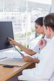Bello infermiere che mostra lo schermo di un computer ad un collega fotografie stock
