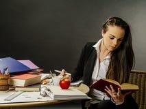 Bello insegnante che si siede alla sua lettura dello scrittorio Fotografia Stock Libera da Diritti