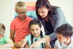Bello insegnante di Yong con il gruppo di bambini del clewer a scuola Immagini Stock Libere da Diritti
