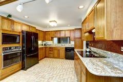Bello interno della cucina con le cime del granito e l'apparecchio nero Immagine Stock Libera da Diritti