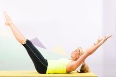 Bello istruttore dei pilates con la stuoia gialla di yoga Fotografia Stock