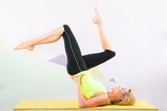 Bello istruttore dei pilates con la stuoia gialla di yoga Immagini Stock