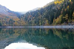 Bello lago circondato dalle montagne e dalle foreste in autunno Malaya Ritsa, Abkhazia fotografie stock libere da diritti