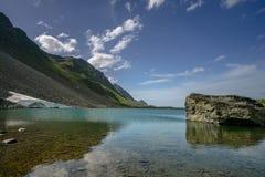 Bello lago della montagna vicino a Tavate con un grande masso nella priorità alta Fotografie Stock Libere da Diritti